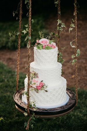 Three-Tier Wedding Cake With Pink Flowers on Swing