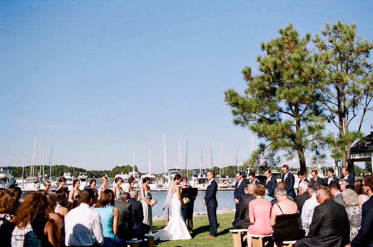 """Megan and Brian's ceremony took place along Osprey Point Inn's shore with the marina and water as the backdrop. A friend played acoustic guitar for the ceremony and even wrote the processional and recessional songs. """"We wrote our own vows, which was one of the most meaningful parts of the day,"""" Megan says. Another moment in the ceremony was when Megan's and Brian's mothers tied fisherman's knots, symbolizing the union of both families."""