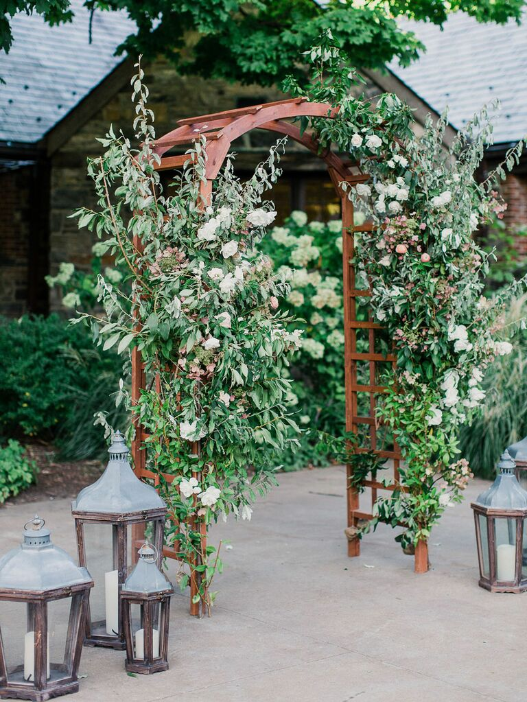 Rustic floral arch at barn wedding entrance with distressed lanterns