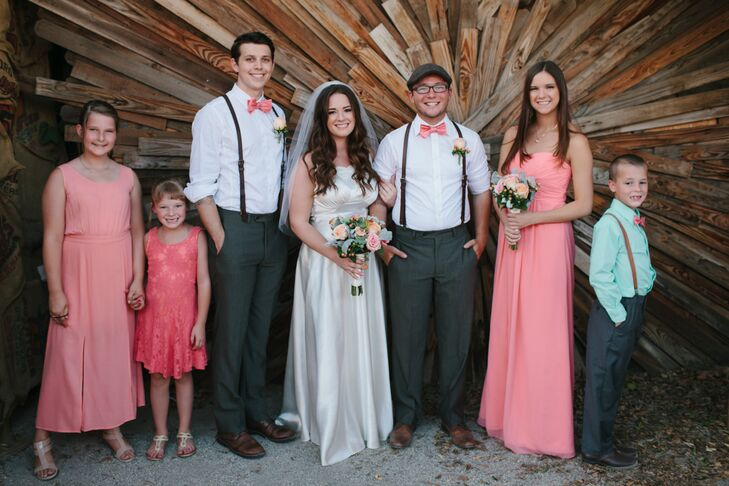 Katie and Dustyn stood among their wedding party, dressed in accents of gray and pink that they picked out themselves. The bridesmaid picked out a floor-length pink dress, while the groomsman matched Dustyn and wore suspenders along with a light pink bow tie.