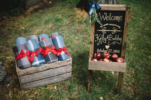 Wooden Welcome Bag Display with Plaid Blankets and Apples