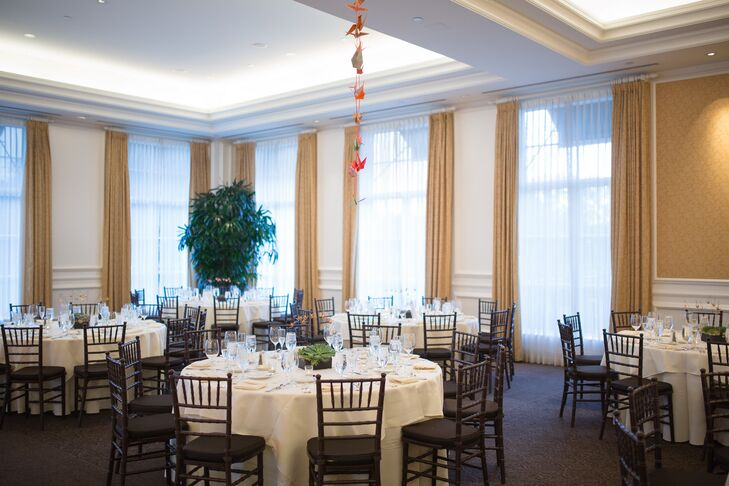 The reception was held inside The Pacific Club, with round tables dressed in white tablecloths surrounded by black chiavari chairs. Japanese paper cranes hung from the ceiling.