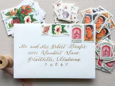 Seashell, white hibiscus, red Mexican independence and Frida Kahlo designs on white envelope with gold calligraphy