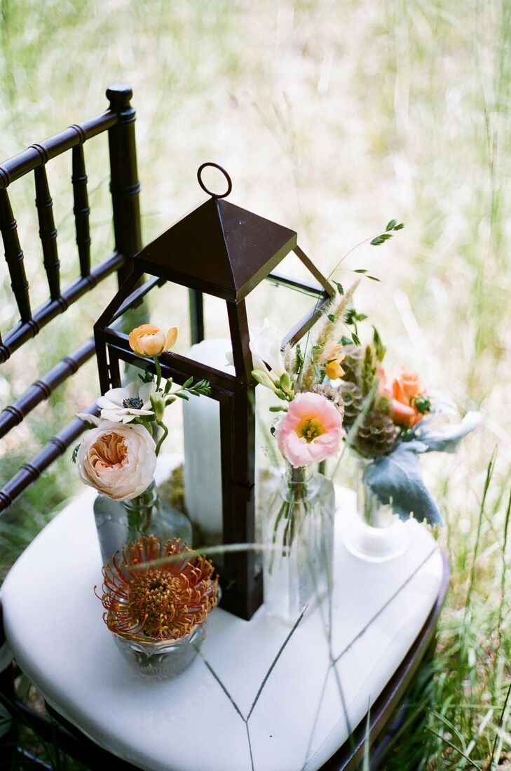 Carriage lanterns and antique bottles filled with small bunches of colorful blooms and rustic accents like wheat and scabiosa pods were arranged at the center of each table for simple-yet-romantic centerpieces.