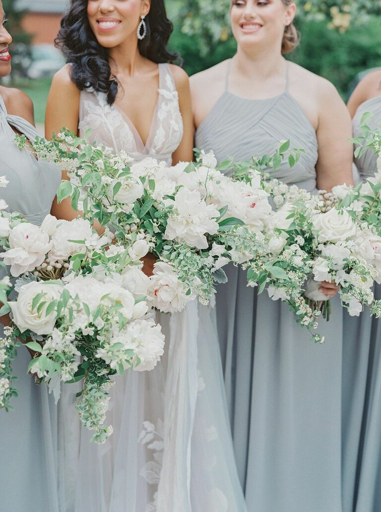 Bridesmaids in gray dresses holding green-and-white bouquets