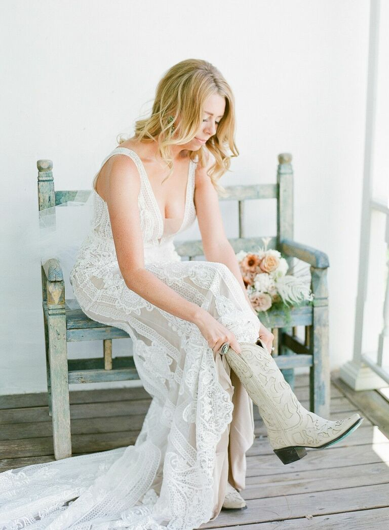 Bride pulling on white cowboy boots