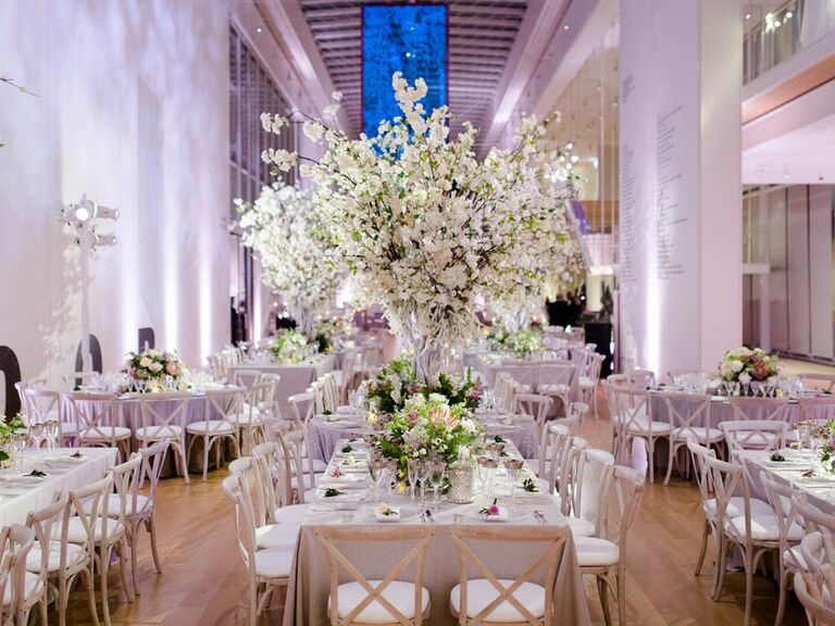 Glam wedding theme at reception with towering white centerpieces and white tableclothes