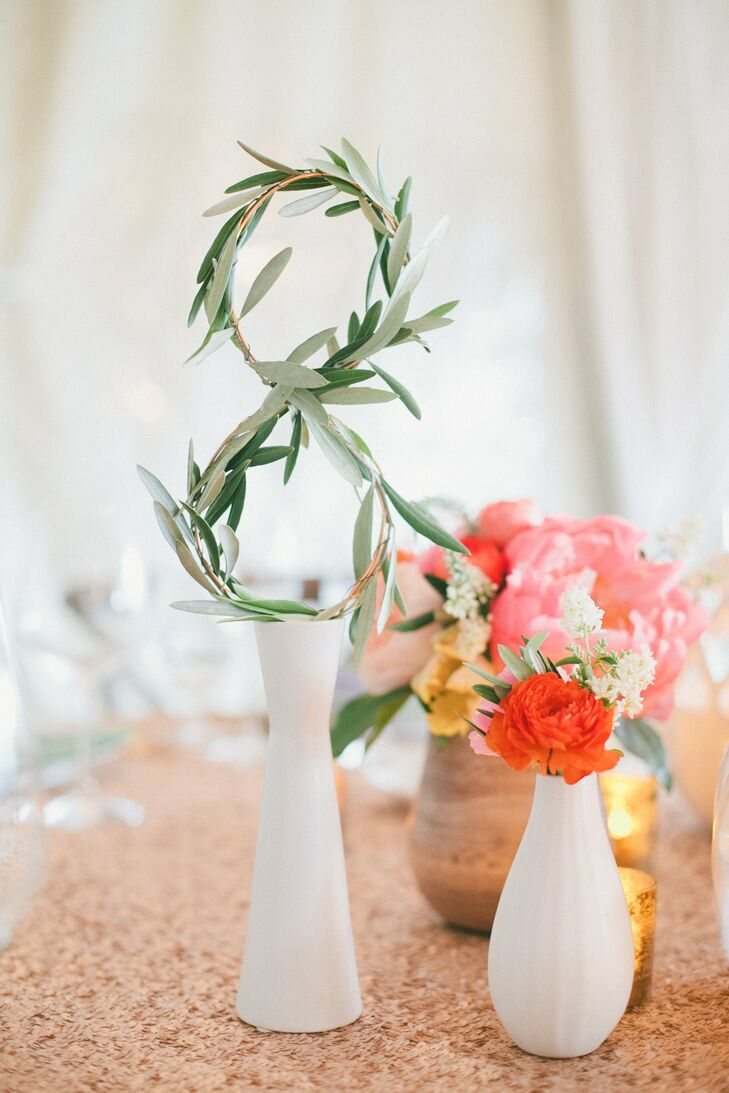 To make the table numbers, JL Designs wrapped olive branches around wire in the shape of each number and then placed them in white ceramic vases.