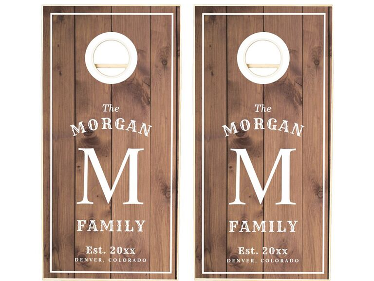 Corn hole set with monogram and family name in simple white type on wooden background