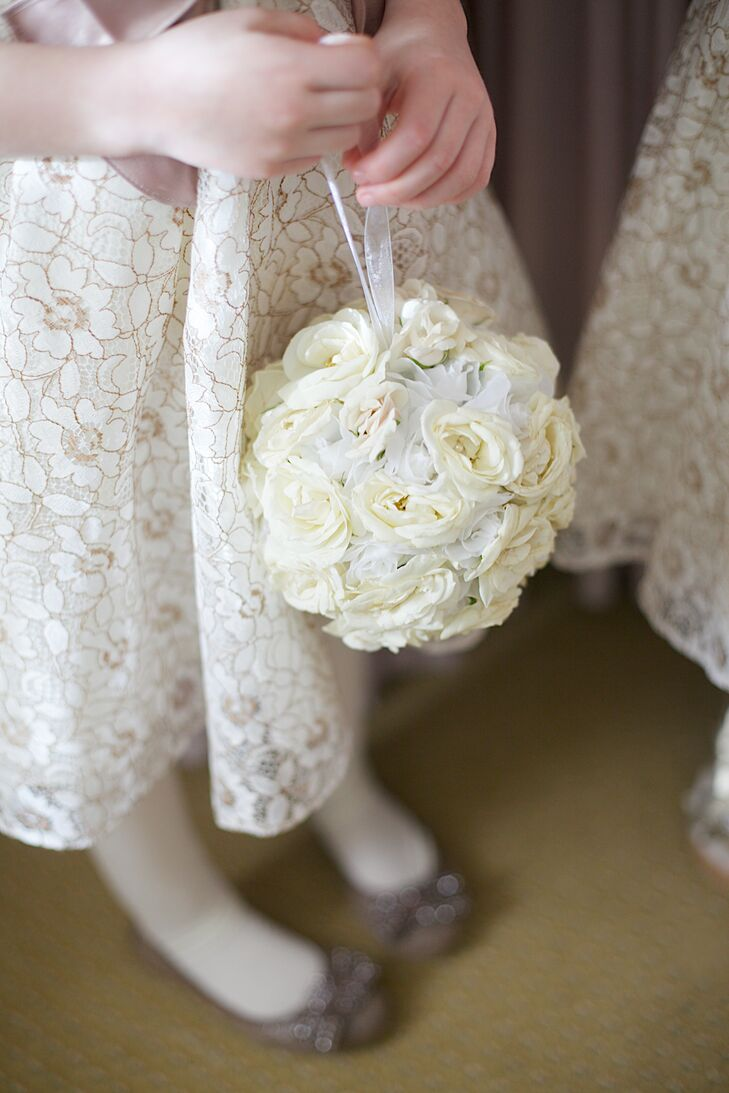 The flower girls wore lace dresses with a floral pattern in gold thread that added a little glamour to their attire. They completed their look with ivory rose pomanders.