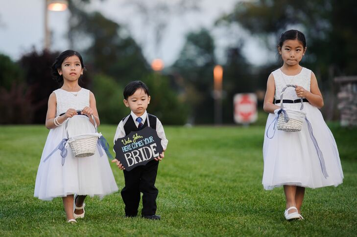 """The flower girls wore white dresses and carried white baskets filled with rose petals while John's nephew carried a chalkboard sign that said """"Here Comes Your Bride."""""""