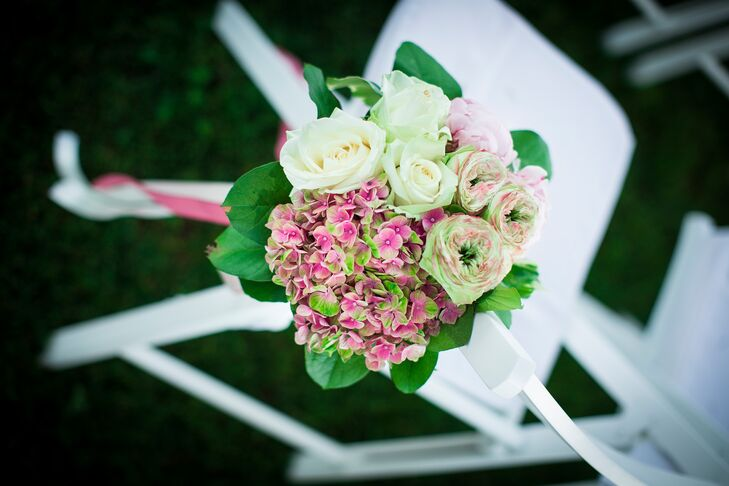 The chairs of the ceremony aisle were decorated with arrangements of green and pink garden roses, ivory roses and green and pink hydrangeas that were tied to the chairs with pink ribbon.