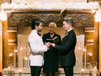 Grooms at altar during ceremony with officiant.