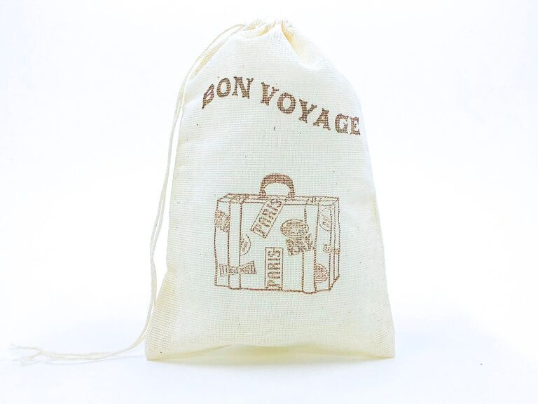 White drawstring bag with 'Bon Voyage' embroidered in sans-serif brown type above embroidered luggage icon