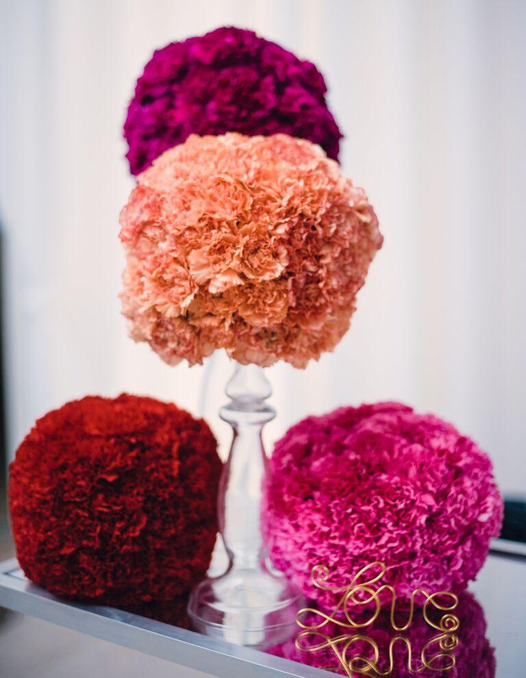Orange, pink, and red carnation pomander wedding decor