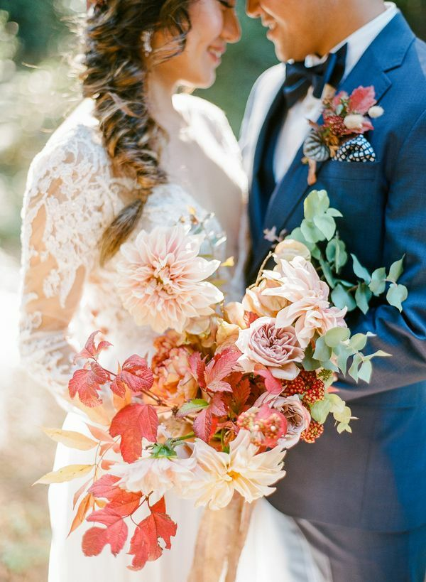 Bride and groom hugging and holding bouquet with leaves and dahlias