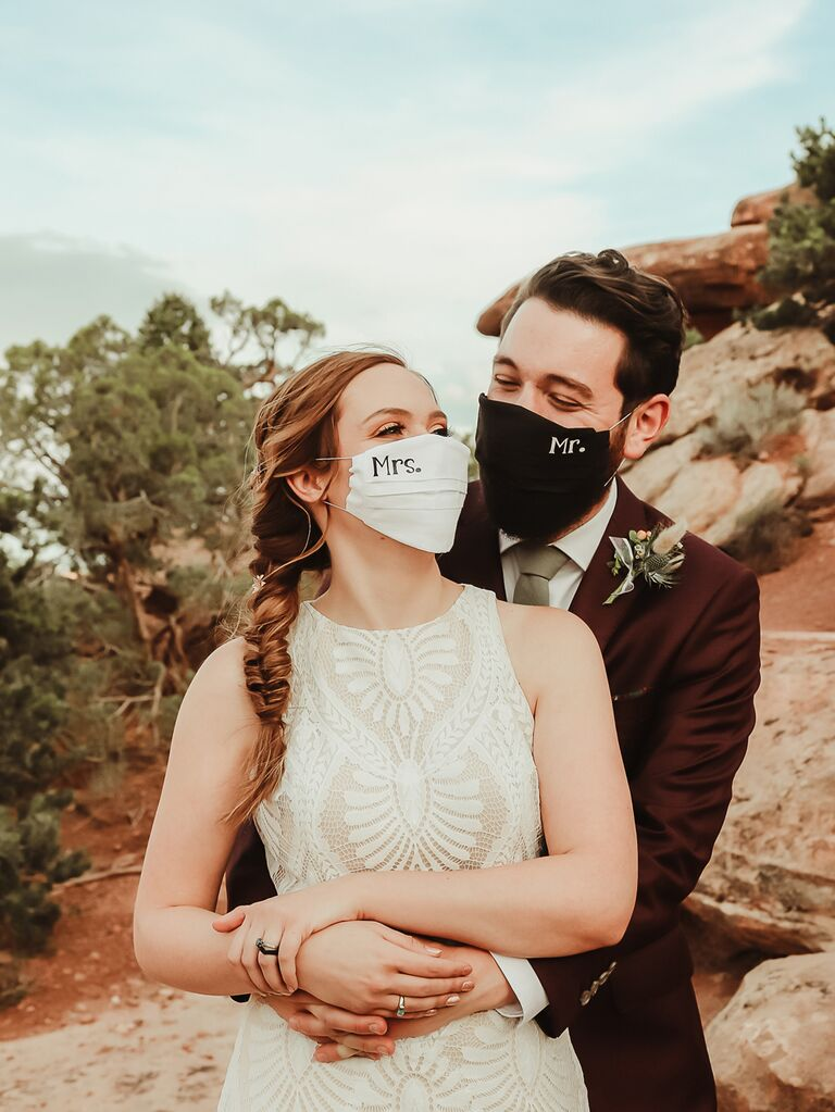 """Bride and groom wearing """"Mrs."""" and """"Mr."""" wedding masks"""