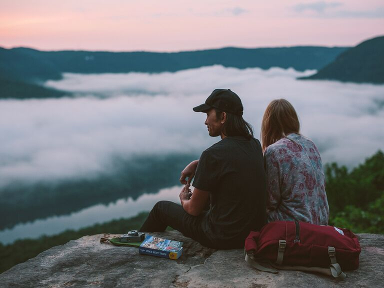 Couple sitting at the top of a mountain