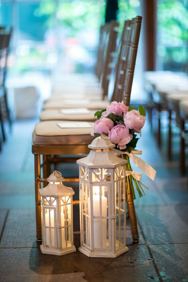 White lanterns with candles and small arrangements of pink peonies lined the aisle.