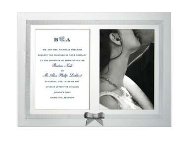 Silver wedding picture frame with invitation and photo of couple