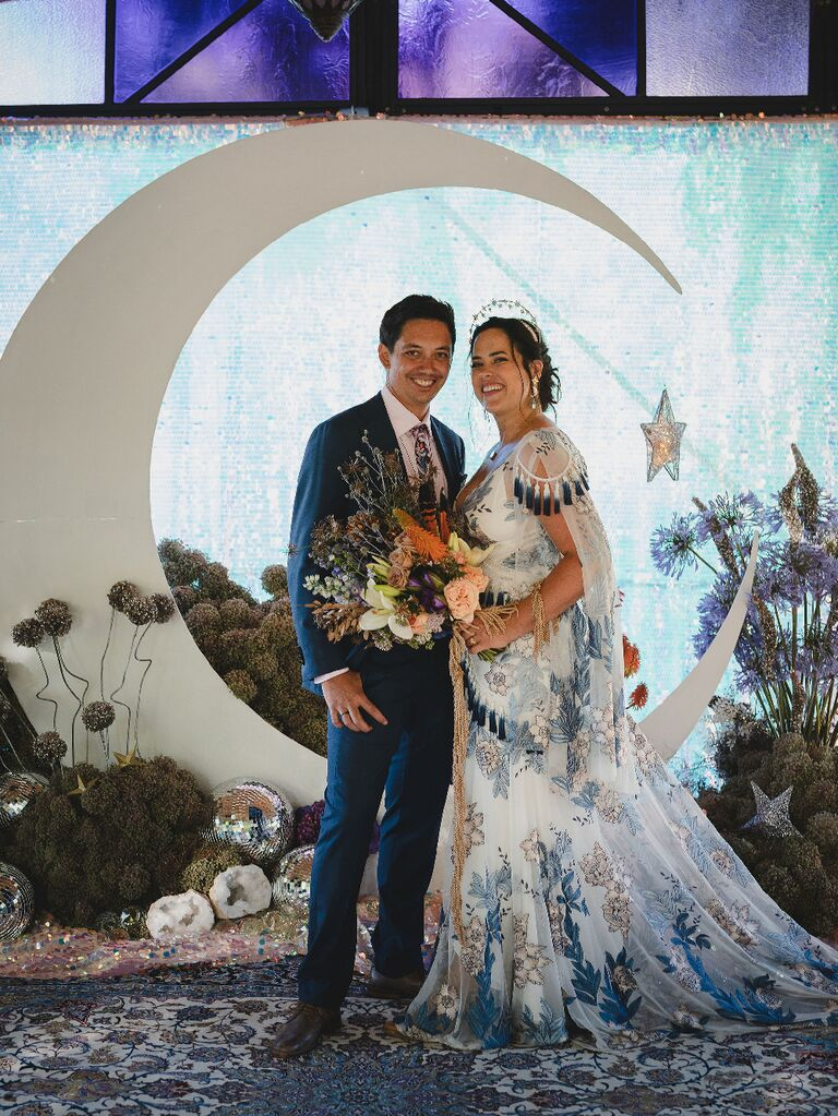 Bride and groom posing in front of crescent moon backdrop at celestial wedding