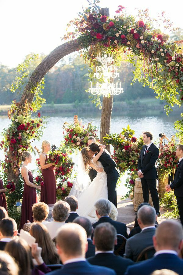 First kiss during lakefront wedding ceremony under arch with chandelier