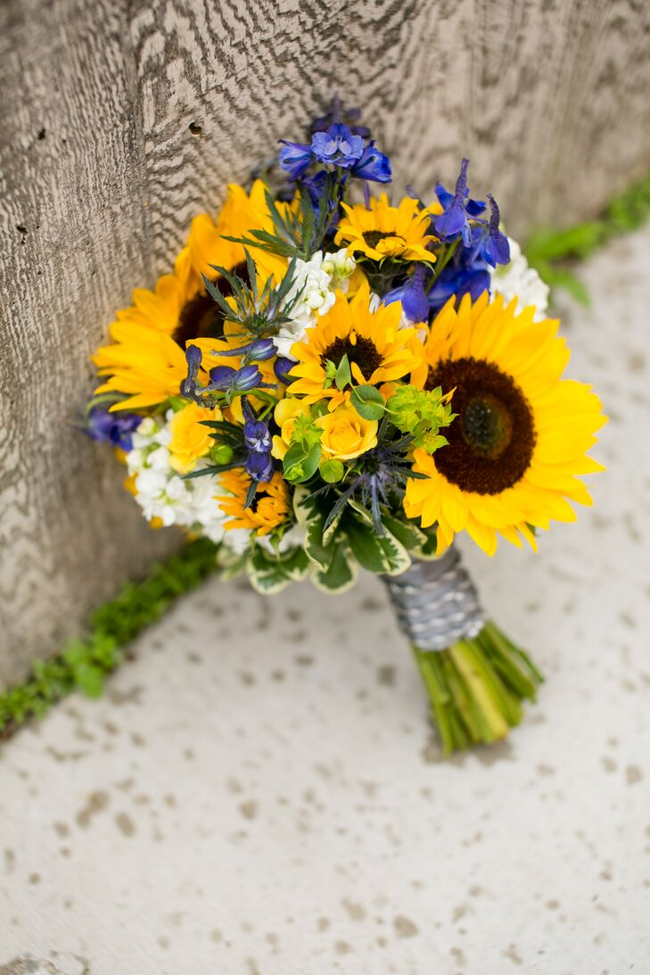 Dawn carried a bouquet with bright sunflowers, blue irises and white stock flowers.