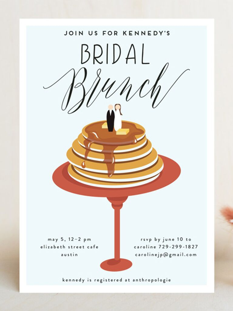 Stack of pancakes with bride and groom topper and event details in minimal black type on light blue background