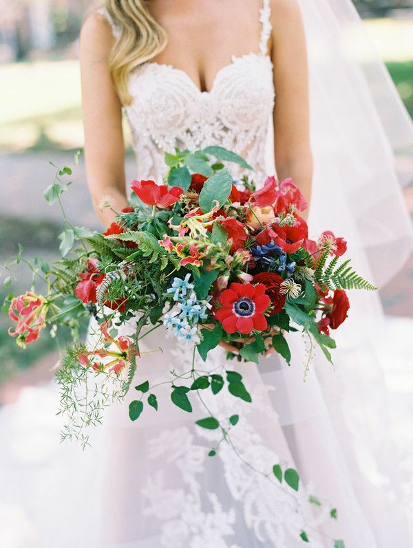 bride holding bouquet with red anemone blooms