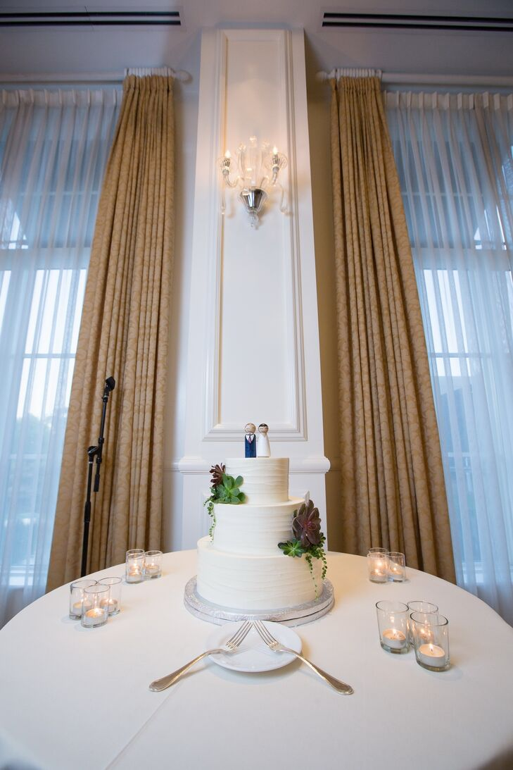 The three-tiered ivory wedding cake was accented with green succulents and had a classic bride and groom cake topper.