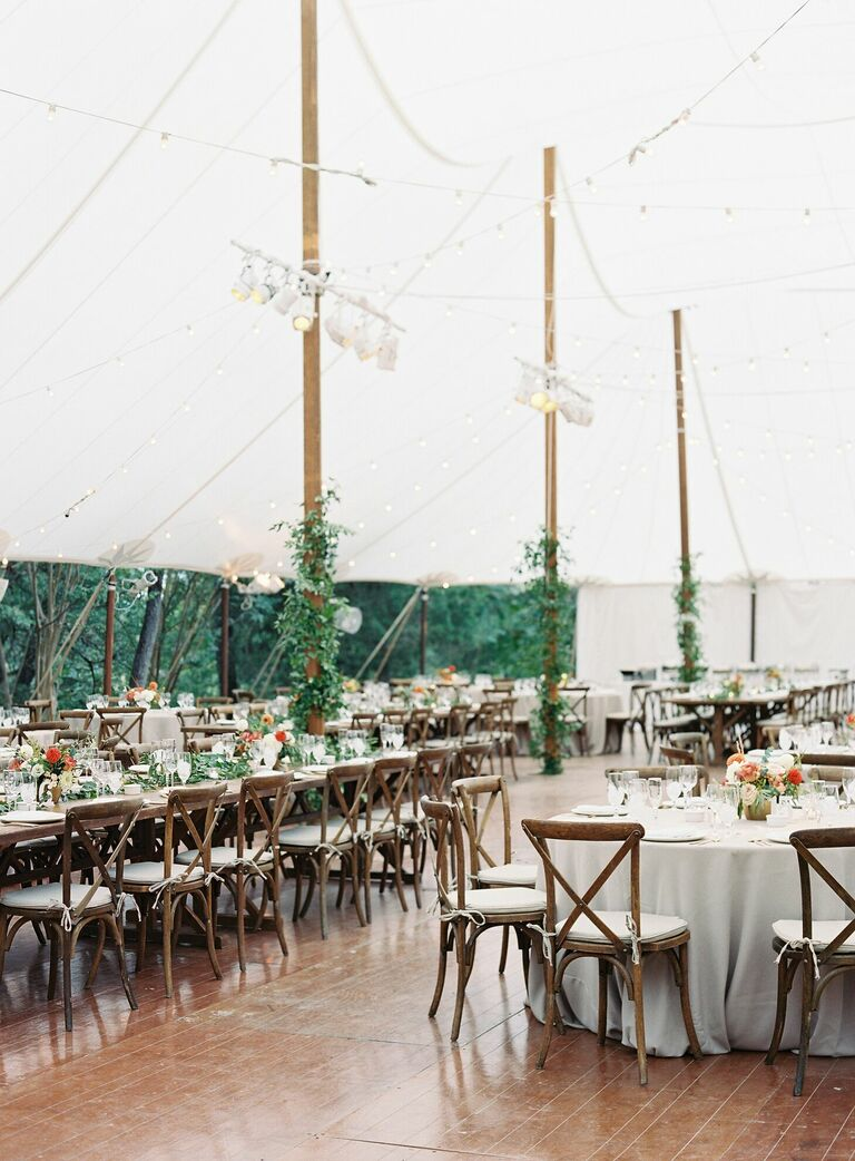 Rustic tented wedding reception with wood cross-back chairs