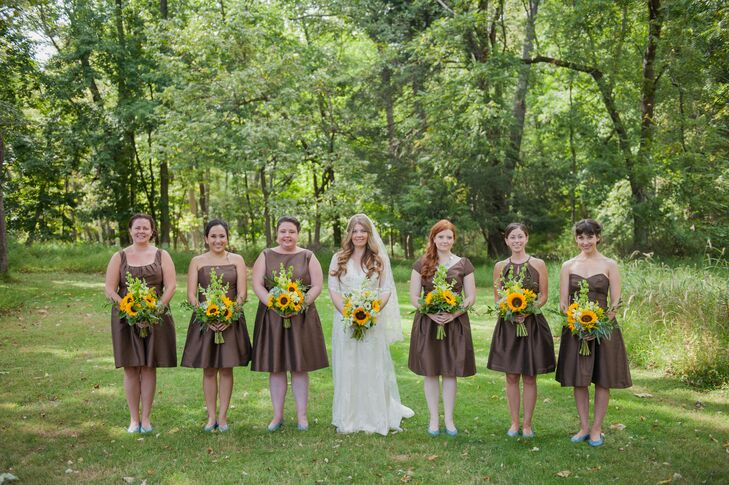 When it came time to select the bridesmaid dresses, Caitlin requested that they choose a dress in chocolate brown. Each woman picked a knee-length dress from the Dessy Group in brown satin and completed the look with fun blue shoes. For a natural and cohesive touch, Mark Bryan Designs also arranged matching bouquets of sunflowers and greenery to finish  the look.