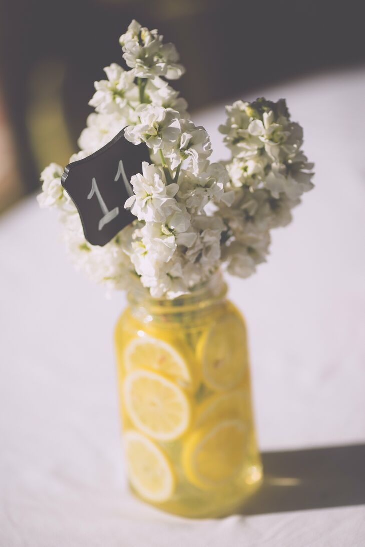 The main color of the wedding was yellow, which the couple chose for it's bright and sweet qualities. The centerpieces, doubled as table numbers, were mason jars filled with lemon slices and blossoming white flowers.