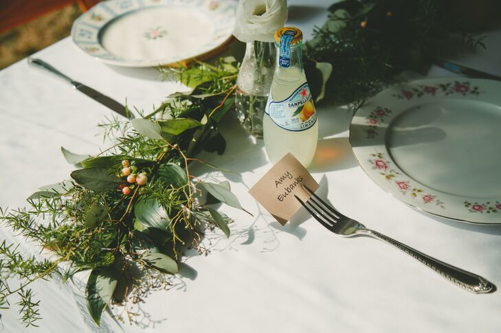 The family style tables were decorated with floral runners, decorated in greenery, and accented with vintage mercury glass and votive candles.