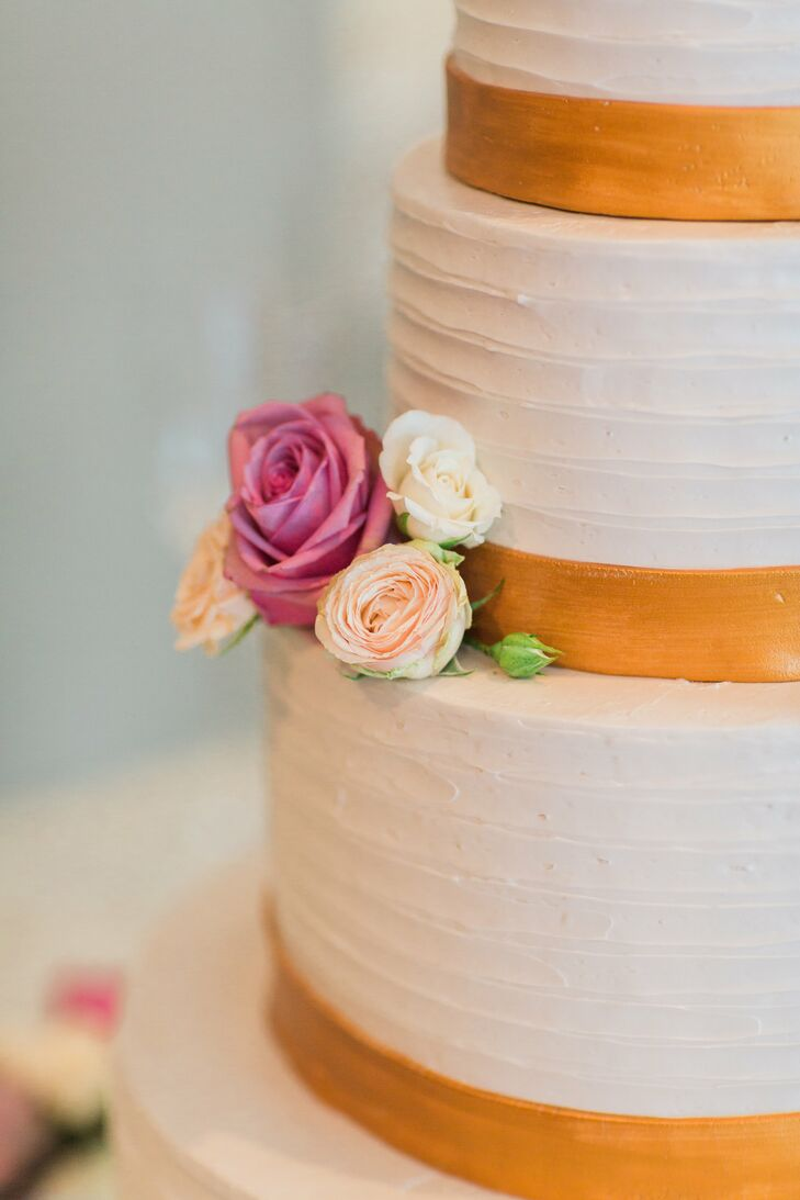 """""""I certainly didn't want ours to be a forgettable cake,"""" Tara says of the orange and white confection. Flavors included a yellow cake tier filled with strawberry and white chocolate and a matcha almond cake for more adventurous guests."""