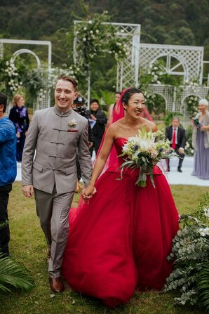 Couple Holding Hands During Recessional With Bride in Red Dress