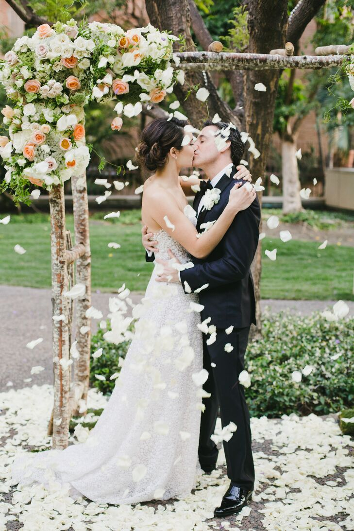As Shannon and Aaron shared their first kiss at Cafe Pinot in Los Angeles, California, the wedding party threw white rose petals.