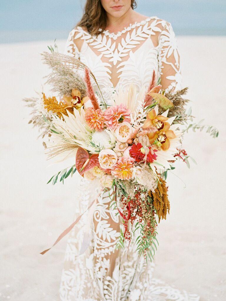 Bride holding boho bouquet on the beach