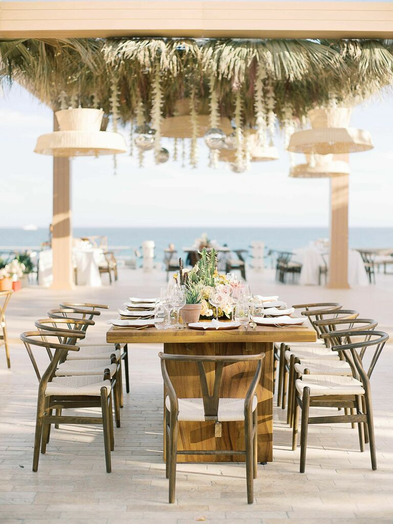 Beachfront wedding reception with large chandeliers and hairpin chairs