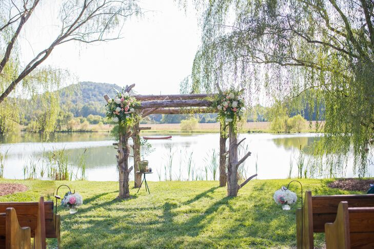 """Morgan and Park exchanged vows under a cedar arch with a lake and mountain backdrop. """"Our ceremony was one of our favorite parts of the day,"""" Morgan says. Guests were seated in vintage church pews, and the aisle was lined with mini floral arrangements hanging in glass vases. """"It truly made it feel like an outdoor church,"""" Morgan says. """"We chose this location because so many of our adventures have taken place outside while camping, hiking, picnicking and exploring. It is our happy place."""""""
