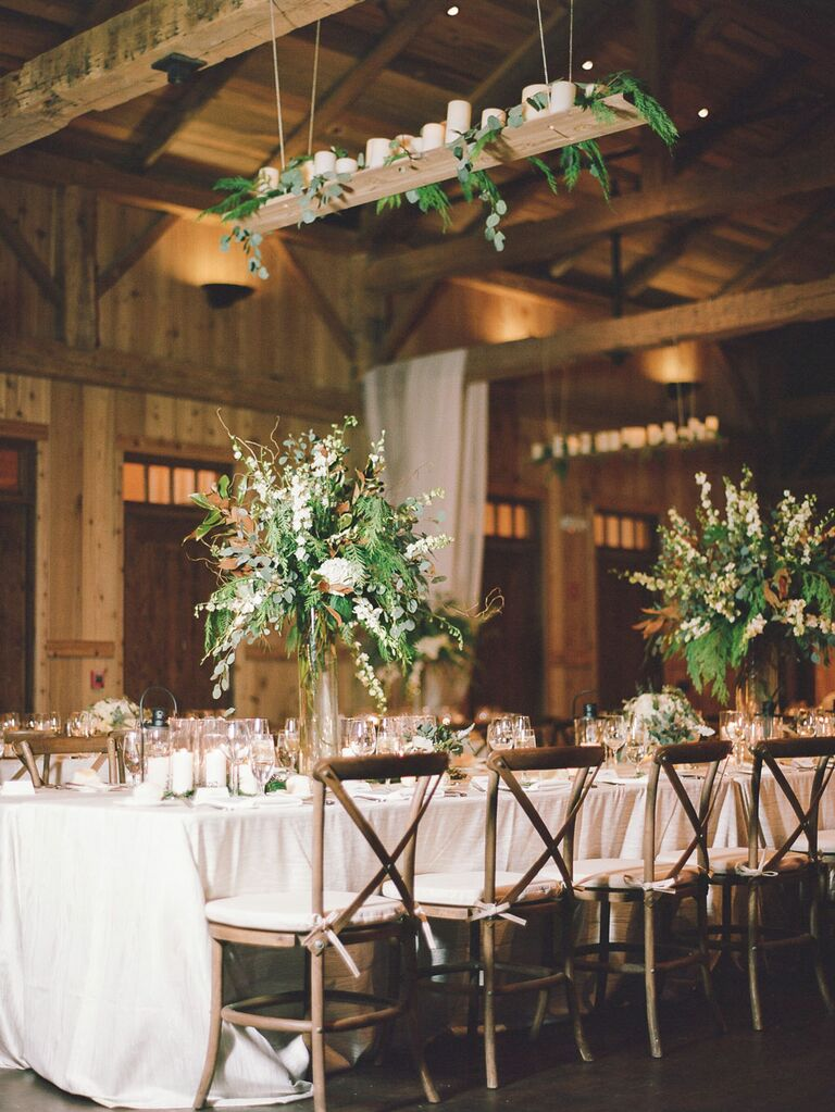 Rustic barn wedding reception with candles on hanging platform above tables