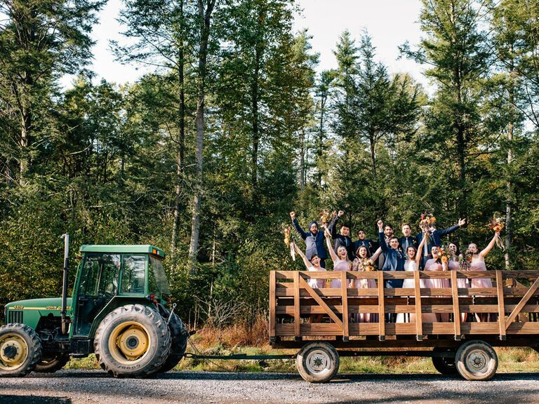 Bride and groom with bridesmaids and groomsmen on hay bale tractor at rustic barn wedding