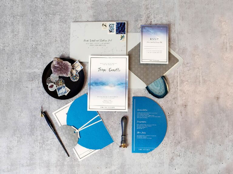 Blue and white celestial-themed wedding invitation suite flat lay