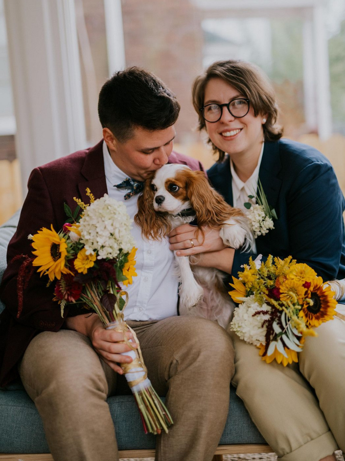 Brides holding dog and sunflower bouquets