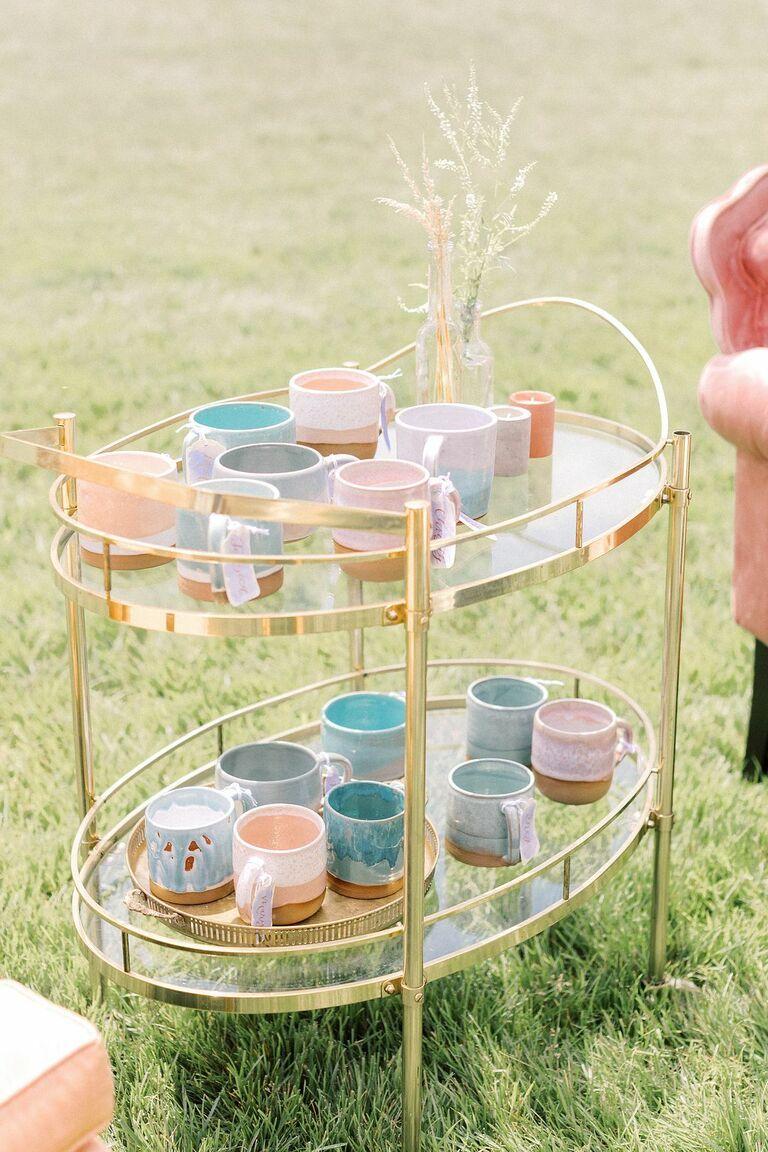 Pastel mugs as escort cards on gold bar cart