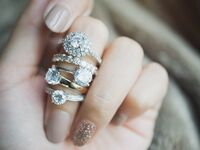 Stack of different diamond engagement ring shapes on finger