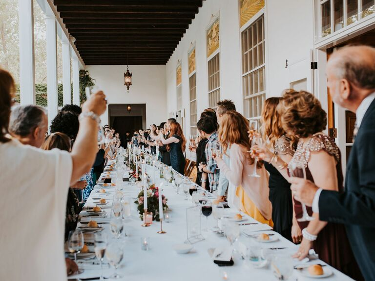 Guests toasting during maid of honor speech at wedding