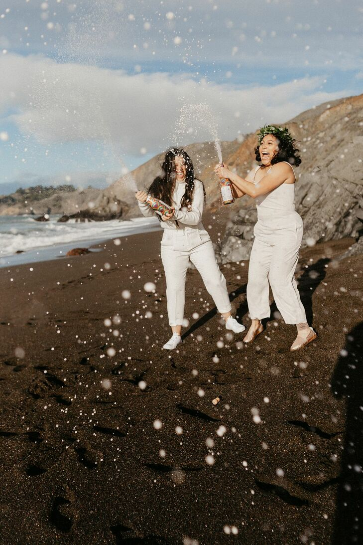Couple Popping Champagne During Sunrise Elopement on the Beach in San Francisco, California