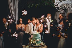 Guests with Sparklers as Couple Cuts Blue Round Tiered Cake