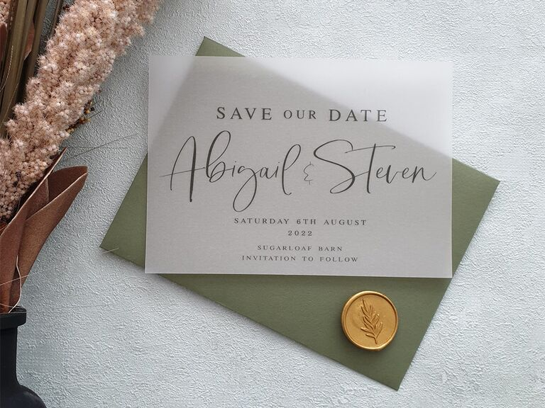 Translucent cover with event details in black type and couple's names in calligraphy with green envelope and gold wax seal